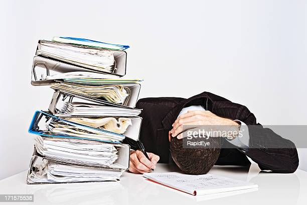 Exhausted businessman with too much work collapses over desk