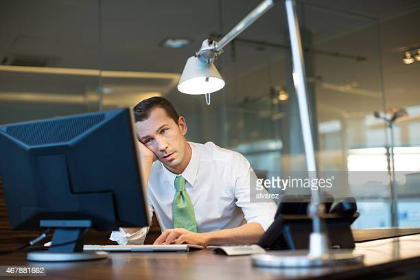 Exhausted businessman working overtime