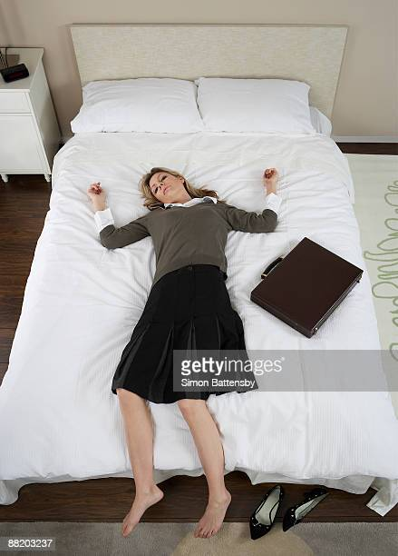 exhausted businesswoman lieing on bed - esher stock pictures, royalty-free photos & images
