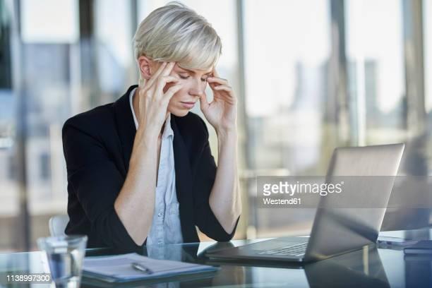exhausted businesswoman sitting at desk in office with closed eyes - cabelo curto comprimento de cabelo imagens e fotografias de stock