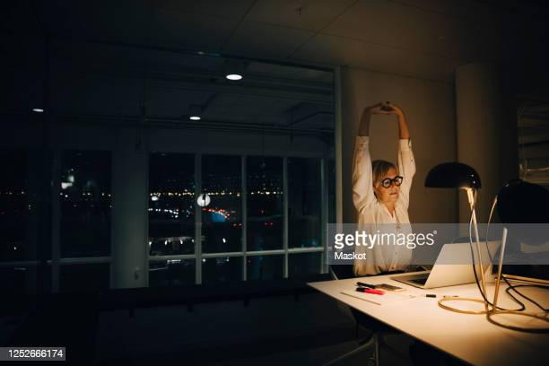 exhausted businesswoman stretching with arms raised while working late in illuminated coworking office - overworked stock pictures, royalty-free photos & images