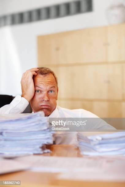 Exhausted clerk sitting with head in hand