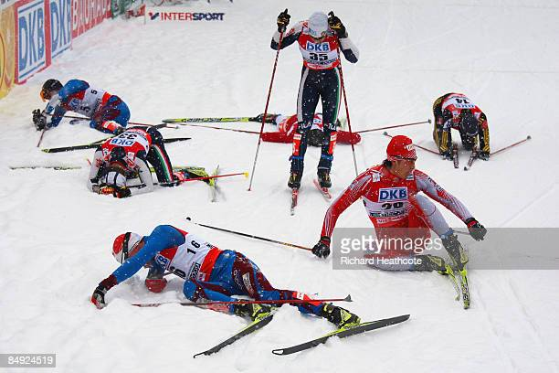 Exhausted competitors lie in the snow after crossing the finish line during the 10km Mass Start race of the Nordic Combined event at the FIS Nordic...