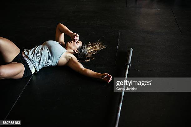 Exhausted cross training athlete resting on floor