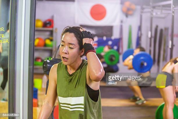 exhausted female cross training athlete rests after a weightlifting workout - circuit training stock photos and pictures
