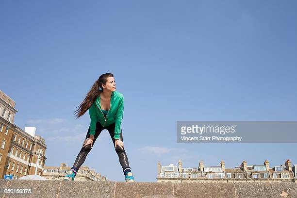 Exhausted female runner standing on wall taking a break