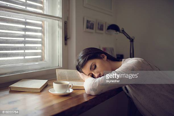 Exhausted female student sleeping on the book.