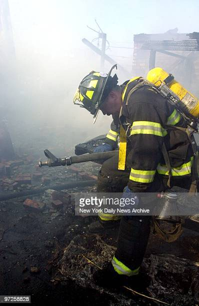Exhausted firefighter takes a break at the scene of American Airlines flight 587 after it crashed in the Rockaway section of Queens