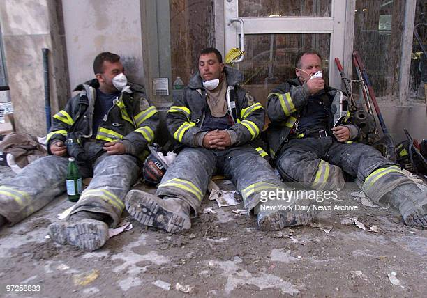 Exhausted firemen take a much needed rest on Broadway during the search for survivors after terrorist attack at World Trade Center
