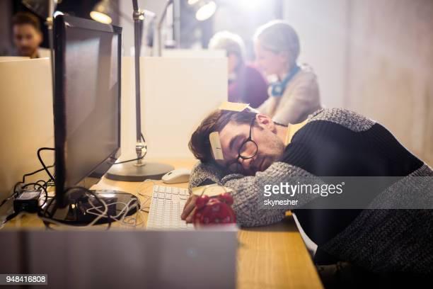 utmattad freelancer sover på skrivbordet på kontoret. - förstoring bildbanksfoton och bilder