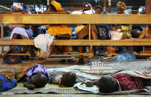 Exhausted from work and hours of praying children sleep beneath the pews while their mothers sleep on the pews at an all night Pentecostal mass held...