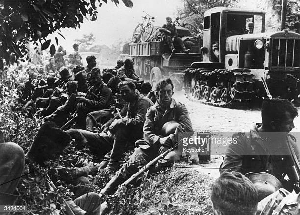 Exhausted German soldiers resting by the roadside on the Eastern Front