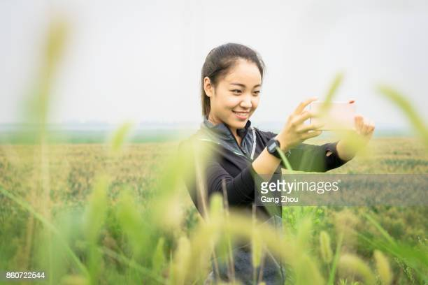 exhausted girl photographing beautiful scenery with smartphone in grassy field