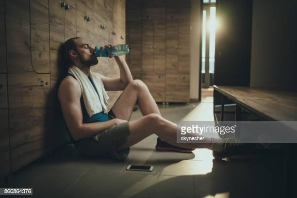 Männlicher Athlet Trinkwasser in Umkleidekabine erschöpft Sporttraining.