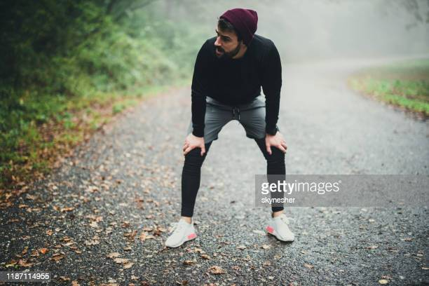 exhausted male athlete taking a break from sports training in nature. - copy space stock pictures, royalty-free photos & images