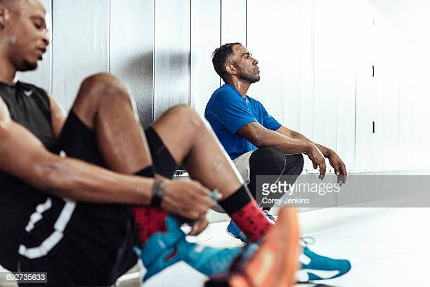exhausted male basketball players taking a break on changing room floor - locker room stock pictures, royalty-free photos & images