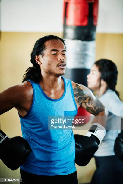 Exhausted male boxer resting after working out on heavy bag in boxing gym