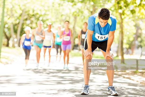 Exhausted Male Marathon Runner With Competitors Running At Park