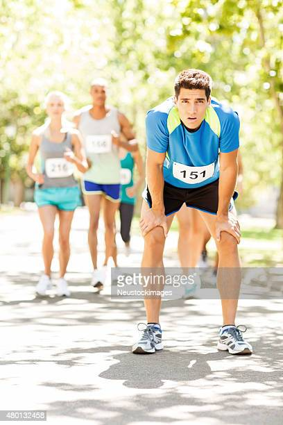 Exhausted Male Marathon Runner With Competitors Running In Park