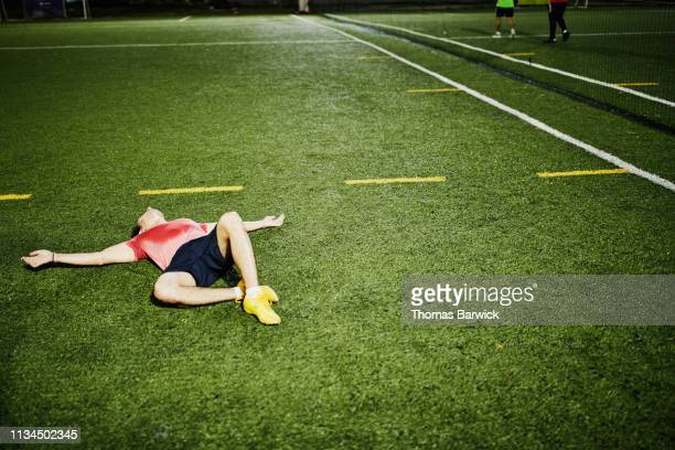 exhausted male soccer player lying on field after evening soccer game - anstrengung stock-fotos und bilder