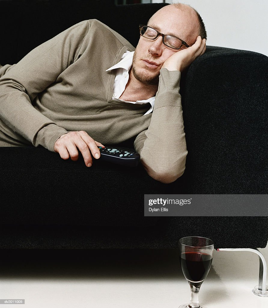Exhausted Man Lies on a Sofa Holding a Remote Control : Stock Photo