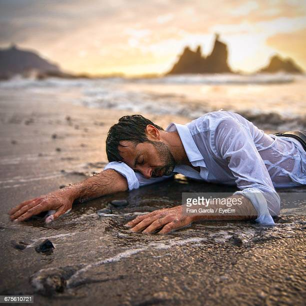 exhausted man on beach after shipwreck - wet shirt stock photos and pictures