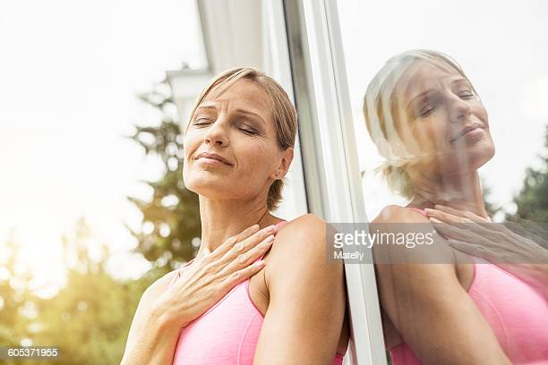 Exhausted mature female runner leaning against patio door