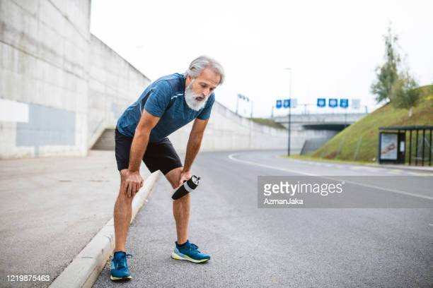 exhausted mature male runner stopping for rest and water - hand on knee stock pictures, royalty-free photos & images