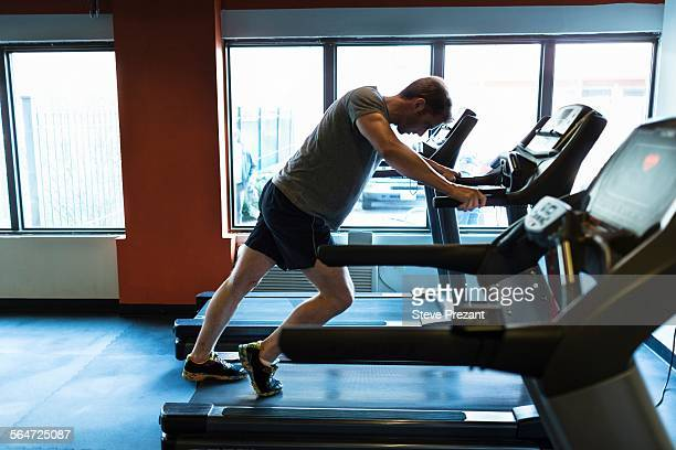 Exhausted mid adult man leaning forward on gym treadmill