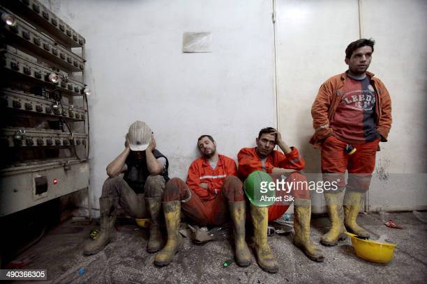 Exhausted miners rest as they await their trapped friends on May 14, 2014 in Soma, Turkey. Rescuers pulled more dead and injured from the coal mine...