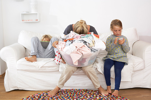 Exhausted mother with laundry basket on couch with children using digital tablet and cell phone - gettyimageskorea