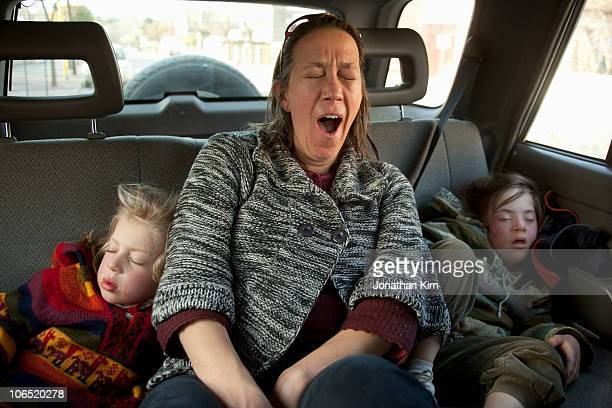Exhausted mother yawns while her daughters sleep.