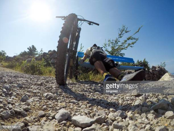 Exhausted mountain biker resting on a bench