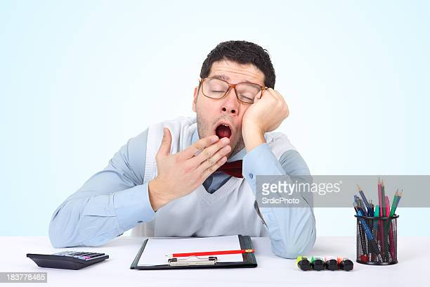 Exhausted nerdy businessman yawning at work in his office