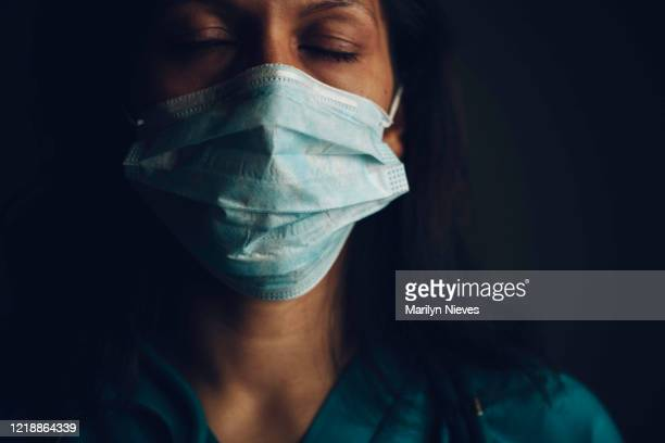 exhausted nurse with tousled hair - essential services stock pictures, royalty-free photos & images
