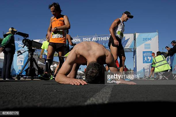 Exhausted runners having just crossed the finish line of the 34th Athens Classic Marathon at the Panathenaic stadium in Athens Greece on Sunday...