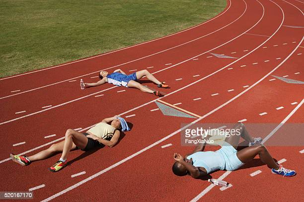 exhausted runners on track - pauze nemen stockfoto's en -beelden