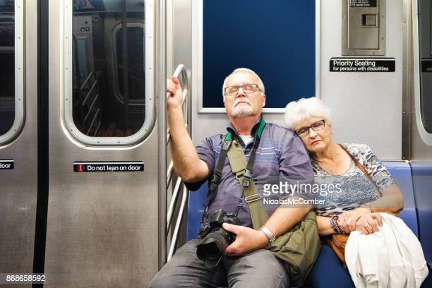 Exhausted senior tourist couple sitting in subway train after a long day