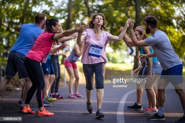 femme senior épuisée salutation avec groupe de supporters après marathon. - marathon photos et images de collection