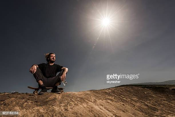 Exhausted skateboarder resting on dirt hill against the sky.