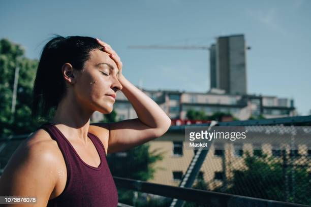 exhausted sportswoman wiping sweat on forehead during sunny day - forehead stock pictures, royalty-free photos & images