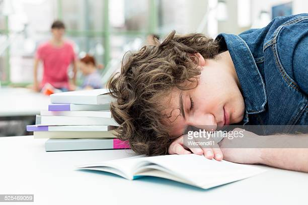 Exhausted student sleeping in a university library