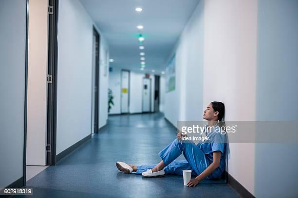 Exhausted surgeon sitting on floor