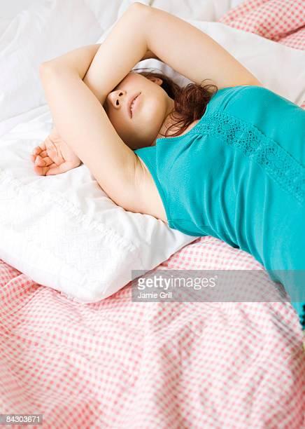 Exhausted teenage girl sleeping on bed