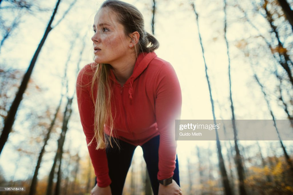 Exhausted woman after jogging in autumnal park. : Stock Photo