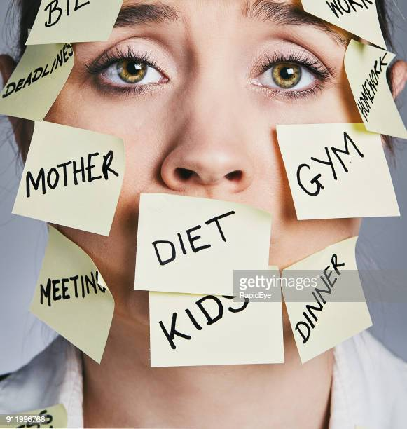 exhausted woman covered in sticky-note chores cannot cope - multitasking stock pictures, royalty-free photos & images