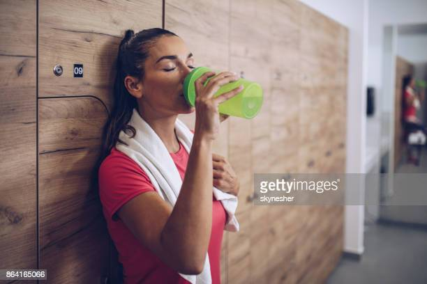 exhausted woman drinking water in locker room after sports training. - thirsty stock pictures, royalty-free photos & images