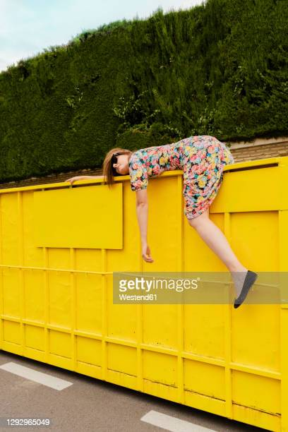 exhausted woman hanging over edge of yellow container - crisis stock pictures, royalty-free photos & images