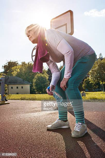 Exhausted woman having a cramp after sports training outdoors.