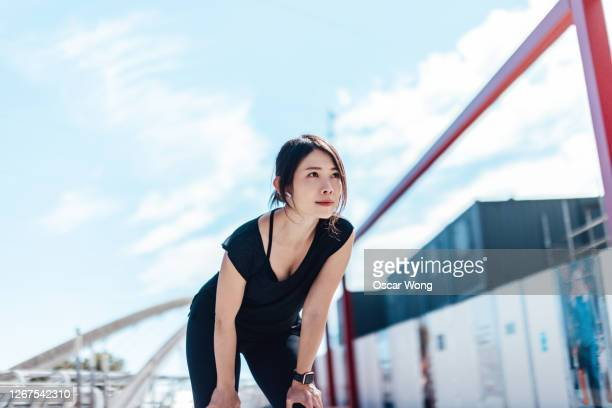 exhausted woman taking rest after fitness workout in the city - injured stock pictures, royalty-free photos & images